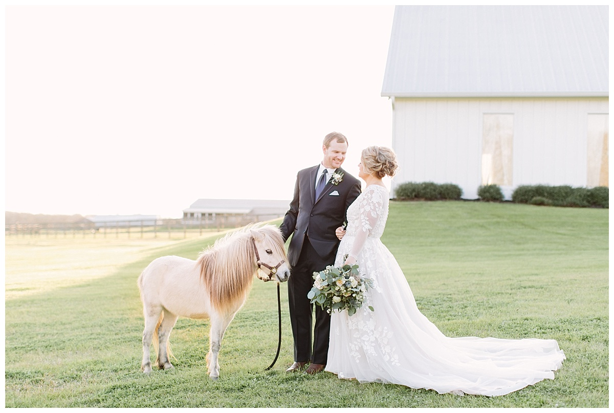 Bride and Groom by chapel with pony gazing at each other | The Farmhouse Events Real Weddings| A Little Something Blue| Kelly & Jarrod