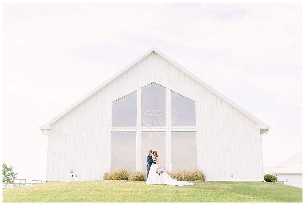 couple in embrace with a backdrop of backside of the chapel The Farmhouse Events Real Weddings| Montgomery TX| Christina & Eric