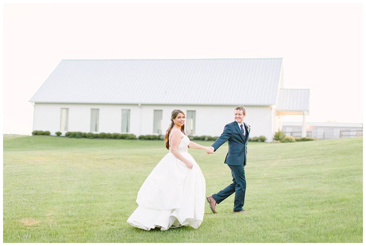 Bride and groom running though fields with chapel in background | The Farmhouse Events Real Weddings| Montgomery TX| Christina & Eric